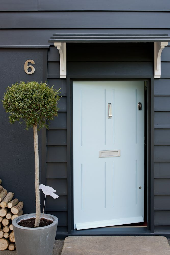 Dark painted weatherboarding with contrasting pale blue front door