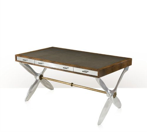 A Louro Preto veneered and aluminium accented Aeronautical writing table, the rectangular top inlaid with a leather writing surface, above three aluminium faced drawers, on polished aluminium propeller supports, each with a brass hub and joined by a brass  stretcher.