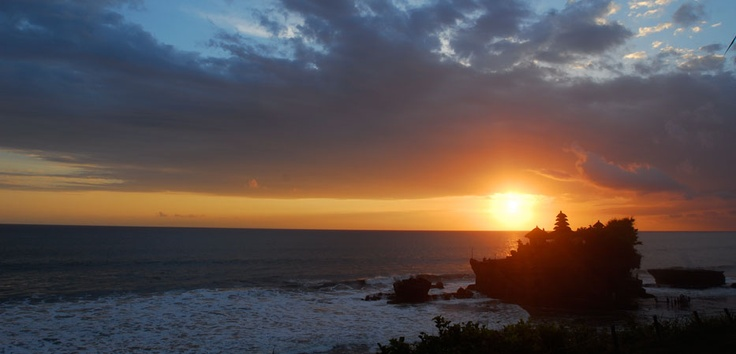 The red sun sets on the horizon, leaving enough light to marvelously silhouette the magnificent Tanah Lot temple.