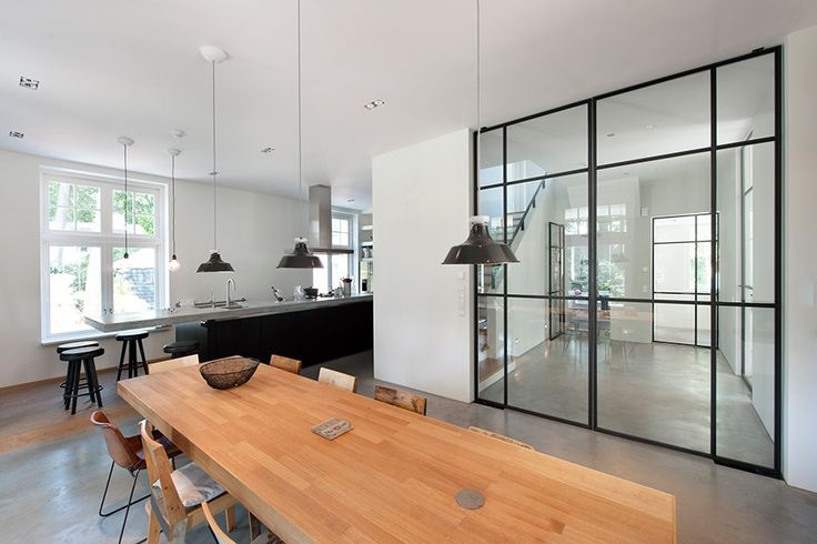 Wood table, black kitchen cabinet and metal pivoting doors (Verbouw monumentale villa Bussum by Vocus Architecten)