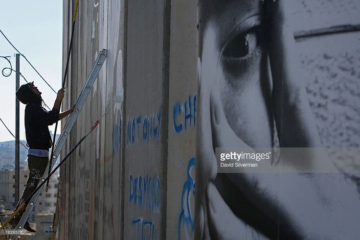 The Italian street artist Blu paints graffiti on Israel's separation barrier December 5, 2007 where is cuts a path into the biblical West Bank city of Bethlehem. Dozens of large-scale artworks by various artists, along with some by elusive British artist Banksy, are part of an exhibition called Santa's Ghetto.