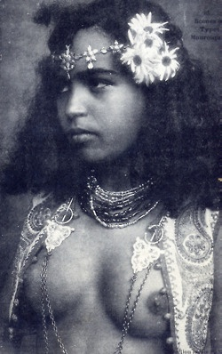 North African girl circa 1910: Beautiful girl from Morocco, wearing flower and traditional jewelry.