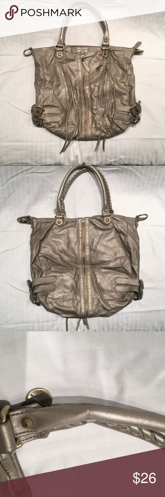 "Big Buddha Silver Zipper Tote Bag Tasseled vegan leather shoulder bag from Big Buddha in pre loved condition. Muted silver color. Exterior in excellent shape outside of one small nick on the handle. A few small stains on the lining. Dimensions: 16""W x 12"" H x 4.5"" D Big Buddha Bags Totes"
