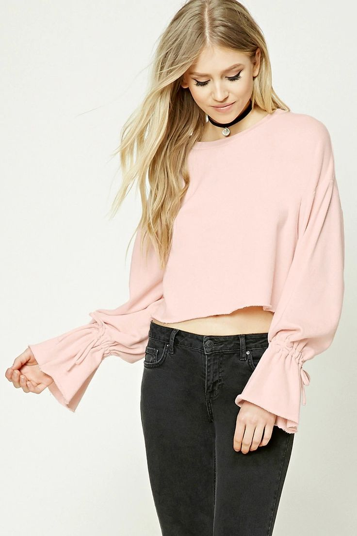 A midweight cropped knit sweatshirt featuring a raw-cut hem, a round neckline, dropped shoulders, long sleeves with self-tie drawstring cuffs, and a French terry lining.