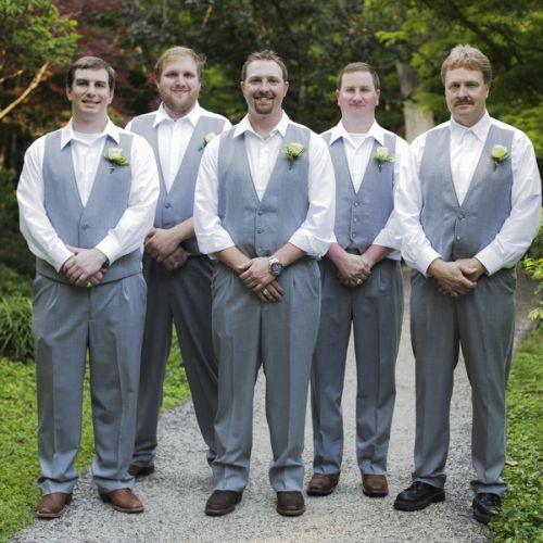 Brad stands with his groomsmen, all wearing matching grey tuxedos from Al's Formal Wear. Brad wore his favorite pair of cowboy boots for the occasion. Image Credit: Fairy Tale Photography