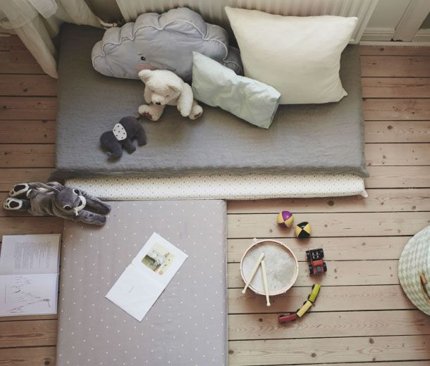 Make an adaptable play space with help of 3 crib mattresses some pillows and soft toys.