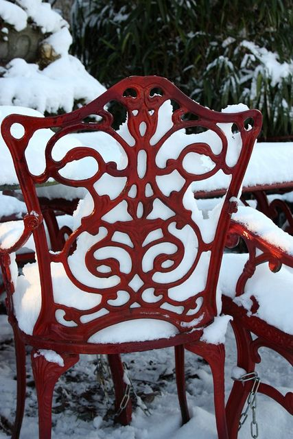 Snow covered filigree chair.