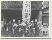 '55年の第1回浅間高原レースの125ccクラスで、発売後間もないYA1が優秀な成績を収めたために、ヤマハのライダーが都内の販売店をパレードした折りに弊社に立ち寄ったもの。看板左にO.A.S.とあるのは、大蔵省認可の保税倉庫の意味。当時O.A.Sを表示できたのはうちと明治屋、それに日本橋の高島屋の3軒でした。しゃがんでいるのは東京ハシロー会の会長(右)と私。ハシロー会は、店のお客さんを中心にしたMCクラブでした。ヘルメット姿の左端が、野口種晴です  別冊モーターサイクリスト[私のアルバムから1]