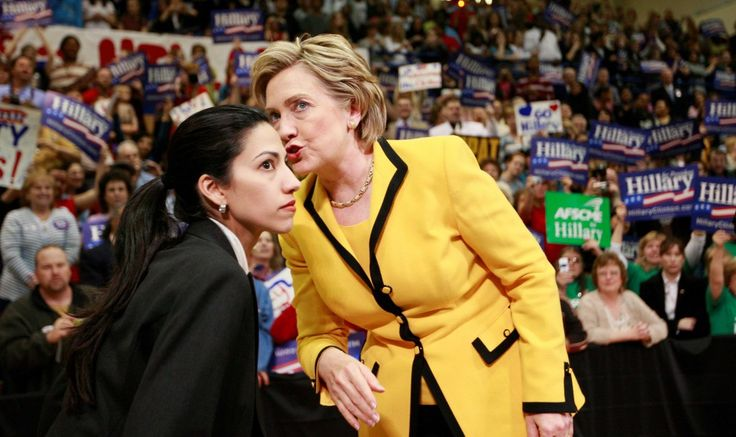 Democratic presidential hopeful, Sen. Hillary Rodham Clinton, D-N.Y., has a word with aide Huma Abedin at the start of a campaign rally at Capital High School in Charleston, W.Va., Wednesday, March 19, 2008. (AP Photo/Charles Dharapak)