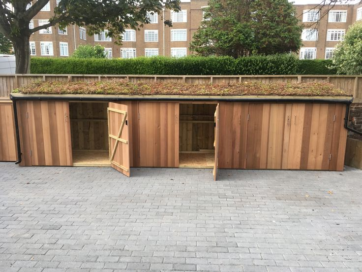 Gigantic cedar clad bike shed which spans 7.5m and has three Classic type units with a single sedum roof, and a bin enclosure to the left