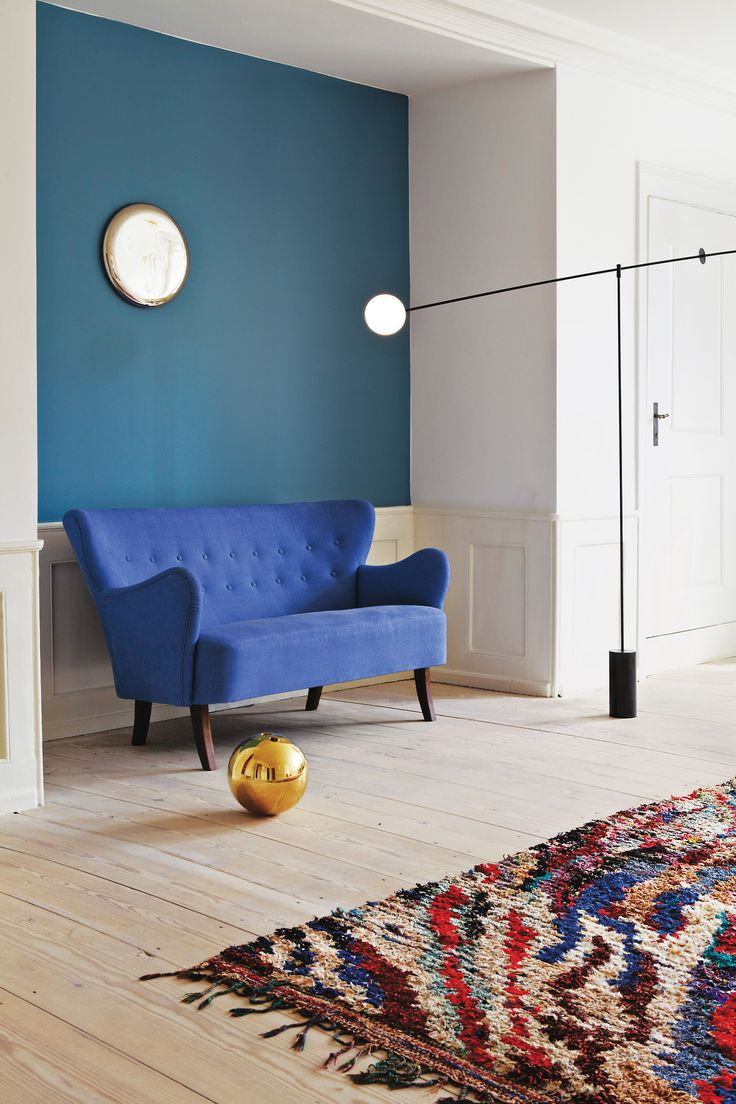 Blue sofa / petrol wall / colorful patterned rug / gold ball object / modern lamp