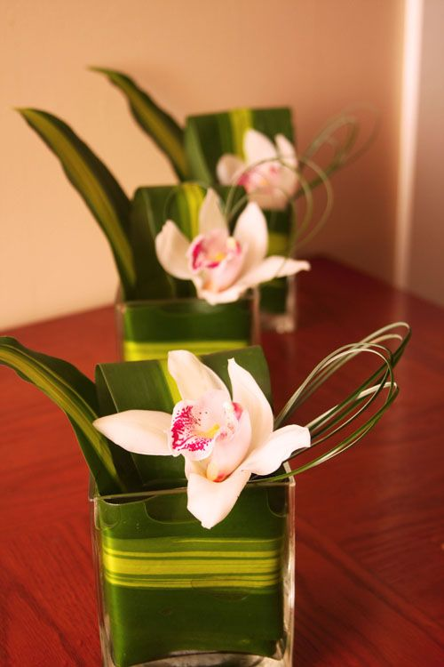 Corn Cane leaves and Cymbidium Orchids, how great would these look on a reception table or cruiser tables?