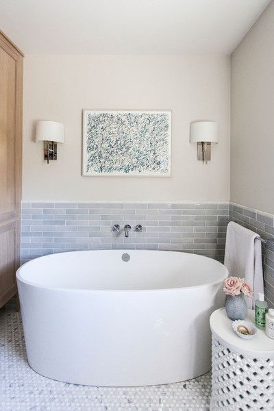 Gray subway tile surrounds a deep soaking tub.