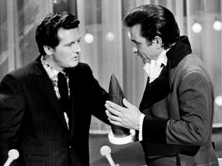 Johnny Cash receives one of his five awards from presenter Jerry Lee Lewis during the CMA Awards show at the Ryman Auditorium on Oct. 16, 1969.
