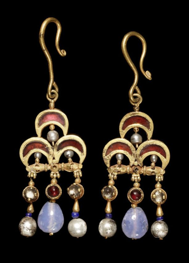Ancient jewlery, Matilde Ruiz Parra,  A pair of Byzantine gold, garnet, pearl, and sapphire earrings  Circa 5th-7th Century A.D. Composed of three crescentic cloissoné garnets, the underside of each crescent with a wire-set pearl, with three pendants hinged below, the central composed of a cabochon box-set garnet with blue chalcedony teardrop pendant, the outer each composed of a cabochon sapphire above a pear-shaped gold element, cylindrical blue glass or lapis bead, and pearl, held in…
