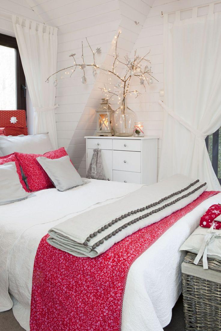 Biała sypialnia zyskała dzięki świątecznym ozdobom – gałązkom w wazonie, wieńcowi, a także czerwonym dodatkom, które ożywiły wnętrze. Sypialnia na co dzień sprzyja wypoczynkowi i wyciszeniu na poddaszu.