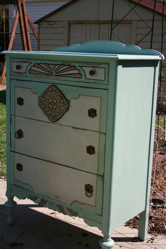 This is a gorgeous Tall Boy dresser painted in blue, gray and a light brown. Weve aged and distressed her to make her look more loved! She has