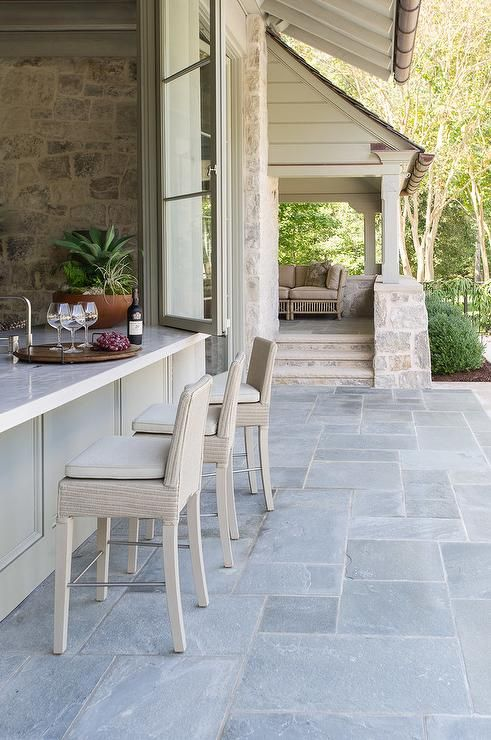 Light gray wicker patio bar stools sit on concrete pavers in front of gray pass through folding doors opening to the kitchen.