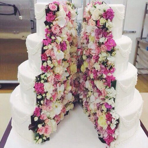 Gorgeous external white wedding cake with pipped detailing. Centeral split layered  with pink and white flowers.
