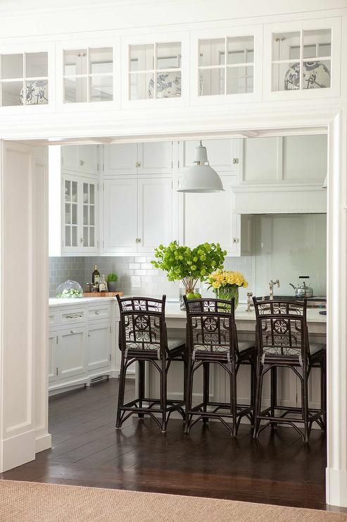 A kitchen doorway is fitted with glass display cabinets leading to a beautiful kitchen filled with white shaker cabinets paired with white marble countertops and a gray subway tile backsplash.