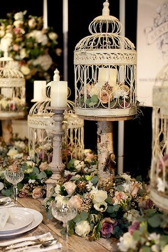 Love bird cages on the table. I like the dynamic arrangement and the candles and candleabras in the mix.