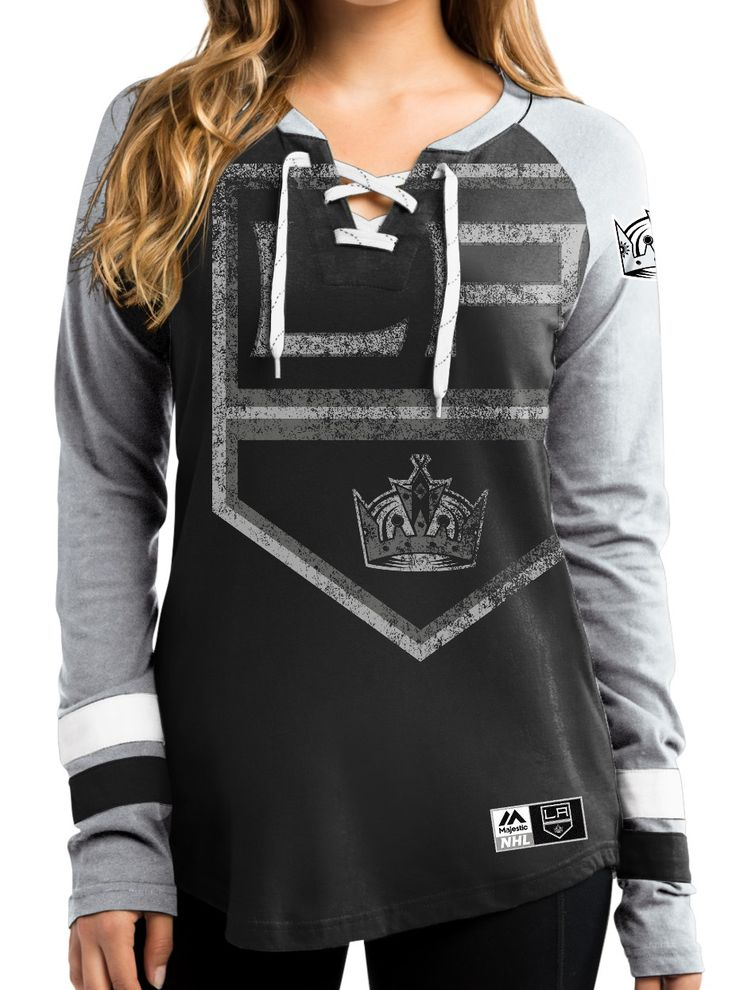 """Support your team in style in this NHL """"Hip Check"""" long sleeve women's t-shirt from Majestic. This lace up v-neck t-shirt features weathered screen printed oversized team logo, woven labels on the left sleeve & bottom hem, primary team color material with contrast color sleeves, set on sleeve stripes, the official Majestic logo and made of 100% cotton. Official..."""