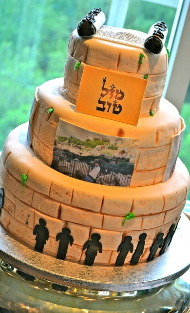 This cake was to celebrate a bar mitzvah that took place at the Jerusalem Wall. The Torah at the top of the cake includes the hebrew portion read during the service, printed in sugar paper. Pictures are also printed in edible sugar paper, and fondant figures resemble people praying at the wall.