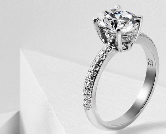An oval-cut diamond rises above a glistening band of pave-set diamonds. The Lilt by Oscar Winter