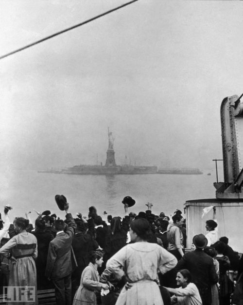 1886: The Statue of Liberty is unveiled. As a gift from France, President Grover Cleveland dedicated our lady liberty in New York Harbor.    Pictured: A group of immigrants traveling aboard a ship celebrate as they catch their first glimpse of the Statue of Liberty and Ellis Island in New York Harbor.