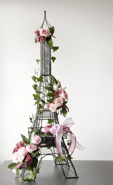 Torre Eiffel floral con estructura de metal. Medida aproximada: 30x30x95 cm. Este arreglo floral estilo creará una atmósfera vintage y artística en eventos soci