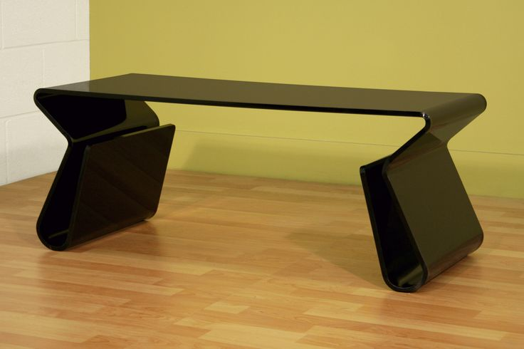 thick black glass table with deep black color coffee and cool glass layer with two legs elongated and there place to keep newspapers