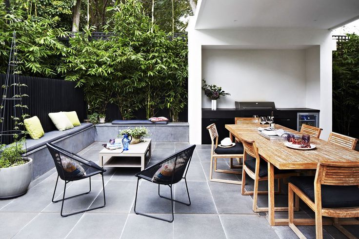 Outdoor entertaining / al fresco area with built-in BBQ, grey pavers and built-in seat, black Acapulco-style wire chairs, green cushions, wooden dining set, bamboo