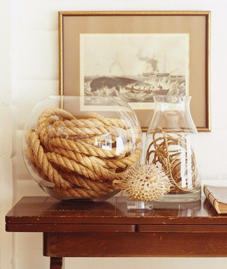 Display rope in creative ways.  To create a vignette like this, cut and coil lengths of rope in glass vessels to showcase their natural tones and coarse textures. An oversized fishbowl pairs nicely with a length of chunky sisal, while a narrower hurricane shows off loops of twine.  To learn how to make your own coiled-rope lamp, view Michael Penney's Online TV DIY segment.