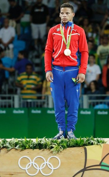 Cuba's Ismael Borrero Molina stands on the podium after winning the gold medal in the men's 59kg greco-roman wrestling event at the Carioca Arena 2 in Rio de Janeiro on August 14, 2016, during the Rio 2016 Olympic Games. / AFP / Jack GUEZ