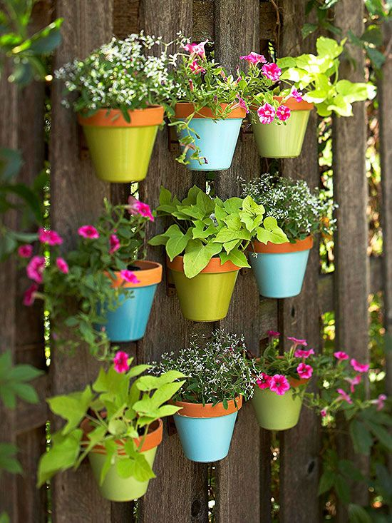 Outdoor Wall Art  Add color to your outdoor decorating with a fence covered with suspended flowerpots. Its wall art for your outdoor room. Start with nine terra-cotta pots and coat the bases with spray paint. Next, plot the grid arrangement and secure pot hangers to the fence. Finish by suspending pots from hangers and filling each container with brightly colored annuals or herbs.