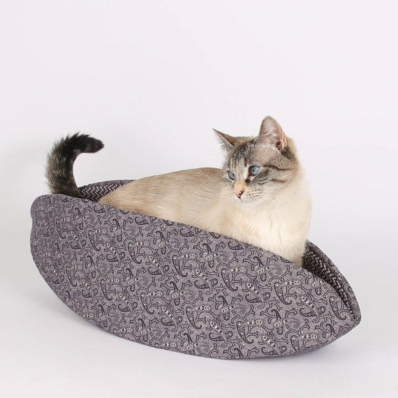 This Goth Cat Bed is made in a Victorian Purple Paisley cotton fabric. Our Cat Canoe® cat bed is a modern pet bed, re-imagined here with a Goth look. Now on sale, the regular price is $32.95  Our Siamese model here is a tiny 8 pound bundle of fluff, but rest assured, the Cat Canoe is capable of holding much larger cats. Unlike the shoe box your cat was living in last week, the Cat Canoe® is made of entirely flexible materials, allowing larger cats total access. They simply squeeze, flatten…