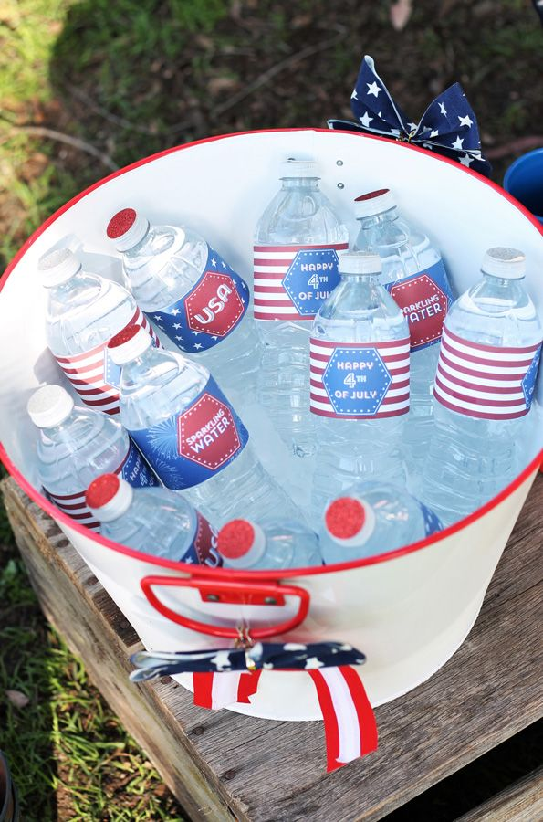 "The last time I was at a vintage flea market, I was able to pick up an old ironing board, a large flag-inspired scarf and a hand embroidered ""Drinks"" banner, all of which made up my drink station. Adults drank tea, lemonade and punch in mason jar glasses and the kids used their patriotic-colored cups. Water bottles with custom labels and some all-American cola in the vintage bottles finished off the drinks. Evite-Party-Ideas-Contributor-Sweet-Jelly-Party-4th-of-July-water-bottles"