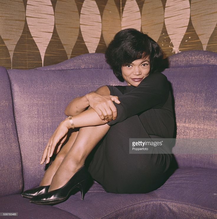 American singer and actress, Eartha Kitt (1927-2008) pictured wearing a black dress and sitting on a couch in 1962.