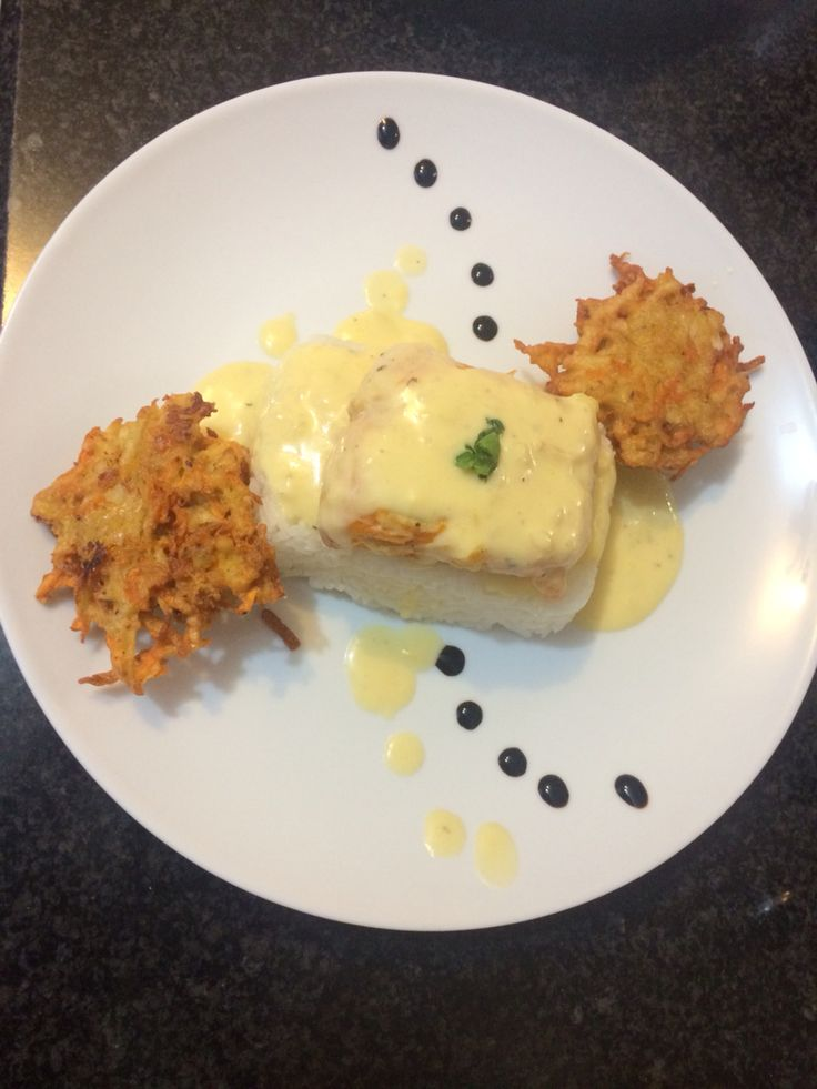 Haddock poached in white sauce with potato fritters.