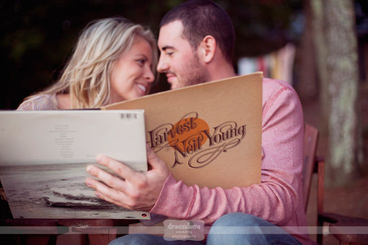 Mixing the indoors with the out... a couple poses with their favorite records while relaxing on adirondack chairs in the woods... from a rustic and outdoorsy engagement photo shoot in Maine...