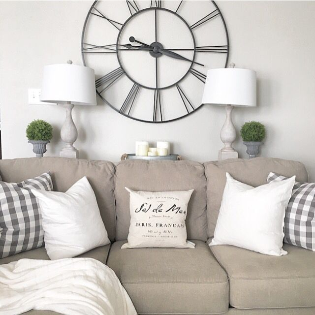 Living Room decor - rustic farmhouse style. Grey sofa, white pillows, grey gingham pattern, large wall clock over sofa | juliecwarnock