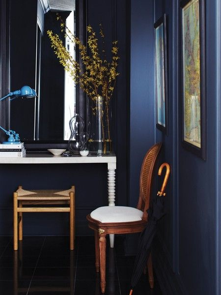 A tall black-framed mirror and forsythia bushes emphasize the height of this small space. DIY panel moulding and vintage finds transformed the basic-condo foyer into a restrained, traditional space.