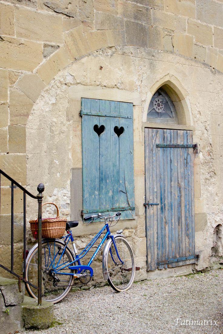 """UN LUGAR FAVORITO.   En mi viaje por la ruta de los Cátaros en Francia...he visto castillos, paisajes preciosos, pueblitos de cuento,...entre ellos me quedo con este rincón, que me da pie a imaginar quién vivirá tras esa ventana con corazones, ...debe ser alguien detallista que ha elegido ese precioso color para su puerta y ventana y que ha combinado su bici para que todo resulte """"de cuento de hadas"""". ¿A quién no le gustaría poder atravesar esa puerta y ver e"""