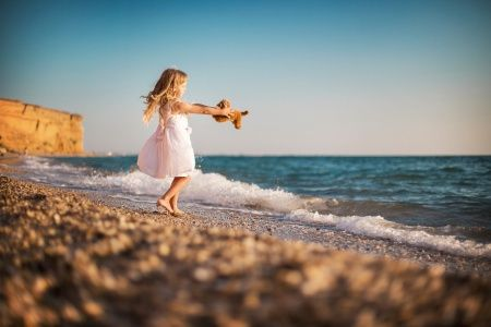Девочка с игрушкой на берегу моря