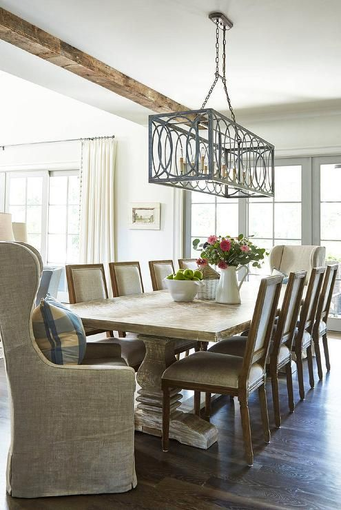 Eight Light Gray French Square Back Dining Chairs Lit By A Iron Rectangular Chandelier Hung From Ceiling Accented With Rustic Wood Beams