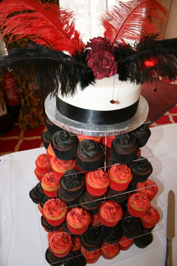 Simple single tier cake with beautiful long feathers, dangling diamonte's and glittery roses to decorate with a combination of black and red cupcakes beneath