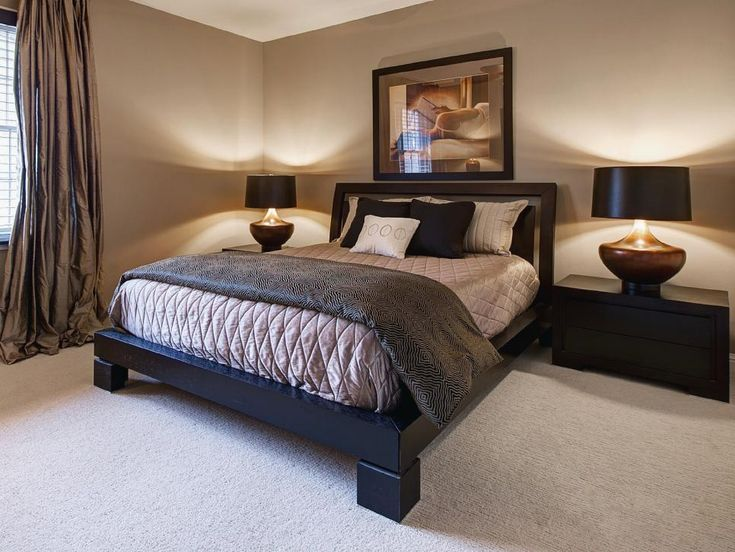 A heavy platform bed anchors this beige bedroom featuring soft lighting, black nightstands and silk drapes.