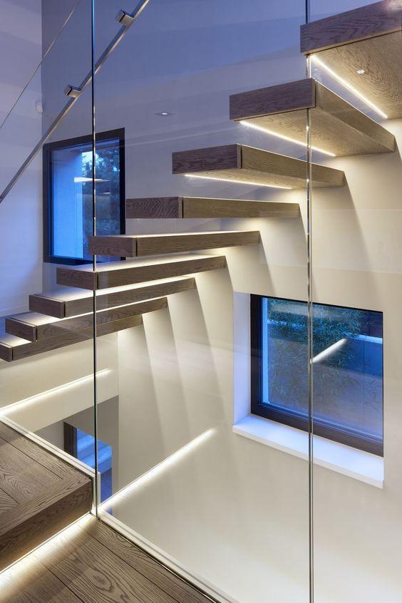 """Iluminação da escada em LEED, de luz branca, iluminando dois """"ambientes"""" simultaneamente, tanto pra quem sobe ou desce a escada que aparece, e ilumina o também o segundo lance abaixo do vidro. Sistema indireto de iluminação:"""