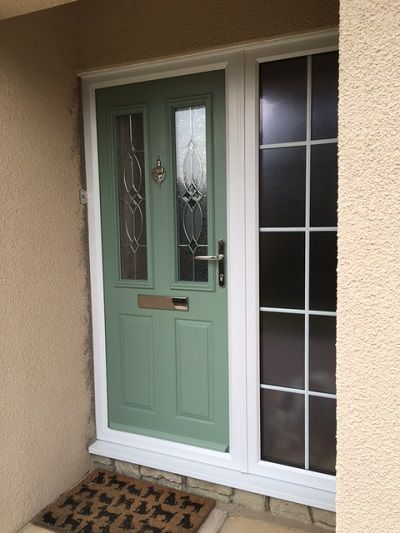 Perfecta Windows - Weston Super Mare Composite Door in chartwell green with white frames and side panel. Finished with stippolyte privacy glass and chrome hardware
