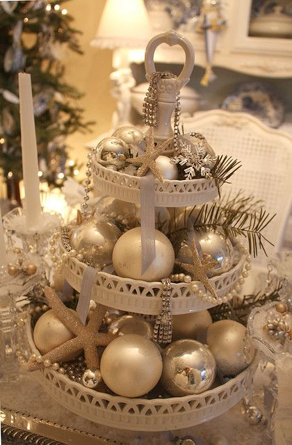 Christmas Centerpiece in white on a dessert tray mix in ornaments, starfish, shells, strands of pearls, vintage jewelry, and evergreen.